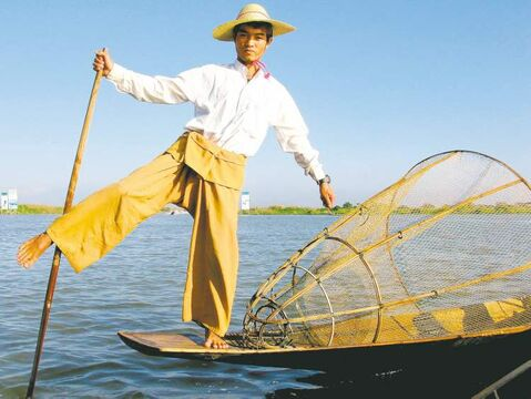 A finely dressed member of the Intha tribe of Inle Lake shows visitors how he and other locals fish, a technique unique to the lake. The fisherman propels the boat by wrapping one leg around the oar. The standing position allows him to avoid weeds and find fish. A conical net is pushed into the shallow waters to trap the fish.