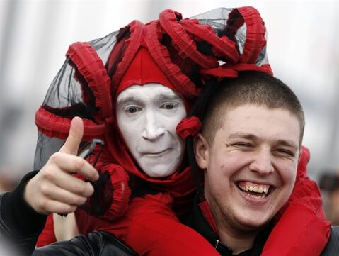 A street performer poses for a picture with a fan in Olympic Park at the 2014 Winter Olympics, Saturday, Feb. 22, 2014, in Sochi, Russia. (AP Photo/Mark Humphrey)