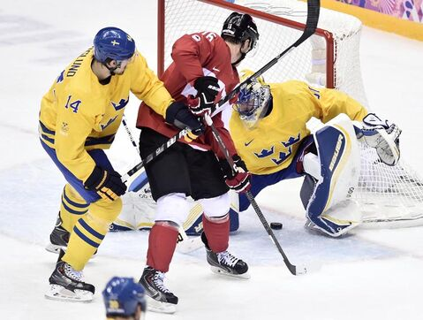 Canada forward Jonathan Toews scores on Sweden goalie Henrik Lundqvist as forward Patrik Berglund back checks during first period action in the gold medal game at the 2014 Sochi Winter Olympics in Sochi, Russsia.