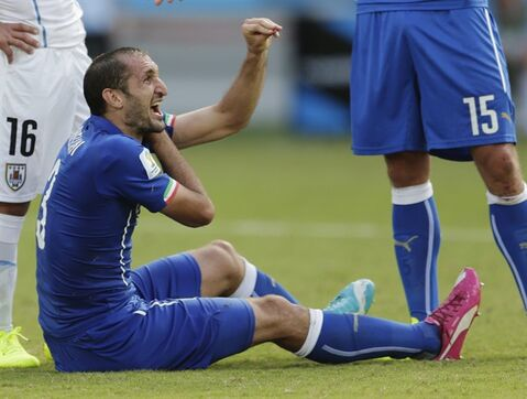 Italy's Giorgio Chiellini complains after Uruguay's Luis Suarez ran into Chiellini's shoulder during the group D World Cup soccer match between Italy and Uruguay at the Arena das Dunas in Natal, Brazil, Tuesday, June 24, 2014. (AP Photo/Petr David Josek)
