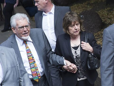 CAPTION CORRECTS THE IDENTITY OF WOMAN AT RIGHT Veteran entertainer Rolf Harris, left, accompanied by his niece Jenny, right, arrive at Southwark Crown Court in London, Friday, July 4, 2014. Australian-born Harris, 84, is due to be sentenced after he was found guilty of 12 counts of indecent assault on four victims aged 19 or under between 1968 and 1986. Harris denied the charges. (AP Photo/Bogdan Maran)