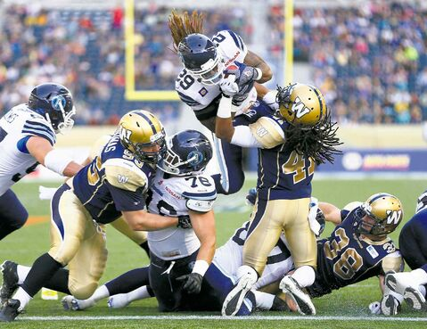 Winnipeg Blue Bombers' Don Unamba (41) can't stop Toronto Argonauts' Curtis Steele (29) flying in for the touchdown during the first half of their CFL pre-season game in Winnipeg Monday.