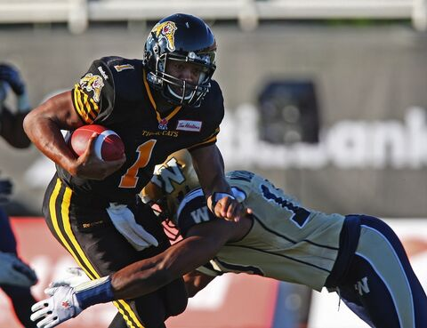 Hamilton Tiger-Cats quarterback Henry Burris is tackled by Winnipeg Blue Bombers linebacker Henoc Muamba during the first quarter.