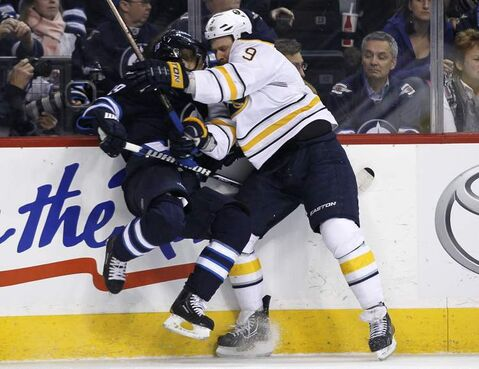 Jets' Toby Enstrom is day-to-day after this smash from Sabres' Steve Ott Tuesday.