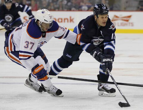 The Jets' Olli Jokinen (12) works his way around the Oilers' Denis Grebeshkov (37) in the second period Tuesday.