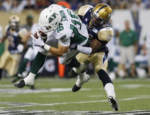 Winnipeg Blue Bombers' Maurice Leggett (31) can't stop Saskatchewan Roughriders' Brett Swain (16) from hauling in the pass Durant during the second half of CFL action in Winnipeg Thursday, August 7, 2014. THE CANADIAN PRESS/John Woods