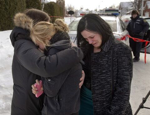 Friends of three people who were found dead in a home comfort each other Tuesday, February 11, 2014 in Trois Rivieres, Que.THE CANADIAN PRESS/Ryan Remiorz
