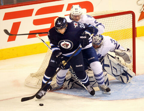 Winnipeg Jet Antti Miettinen works against Maple Leaf defenceman Michael Kosta and netminder James Reimer March 13 at the MTS Centre. The Leafs host the Jets Saturday night.