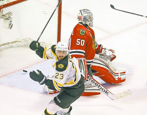 Boston's Chris Kelly celebrates the overtime winner against Chicago in Game 2, scored by teammate Daniel Paille.