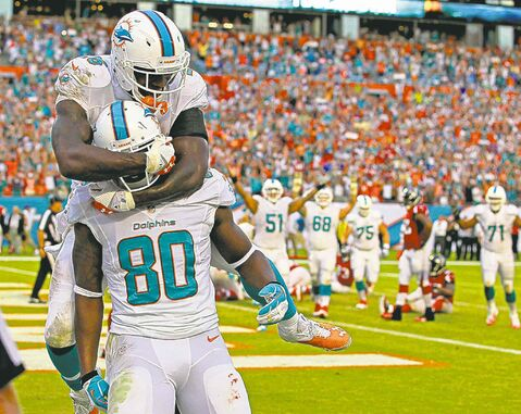 Dion Sims takes a hit from Fish teammate Lamar Miller after catching a TD pass in the fourth quarter.