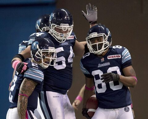 Toronto Argonauts wide receiver Romby Bryant (80) is congratulated by teammates Chad Owens (2) and Chris Van Zeyl (54) after hauling in a touchdown pass against the Winnipeg Blue Bombers during first half CFL action in Toronto on Thursday October 24, 2013. The Argonauts have signed offensive tackle Van Zeyl to a contract extension through the 2016 season. THE CANADIAN PRESS/Frank Gunn