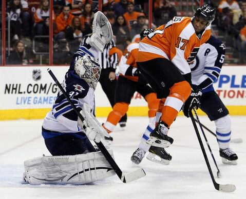 Philadelphia Flyers forward Wayne Simmonds, right, leaps as the puck shot by Claude Giroux gets past Winnipeg Jets goaltender Ondrej Pavelec in the second period of Saturday afternoon's game. The Flyers won 5-3.