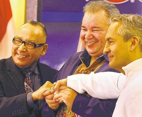 From left, Norway House Chief Ron Evans, MMF president David Chartrand and Sagkeeng First Nation Chief Donovan Fontaine join hands at the announcement.
