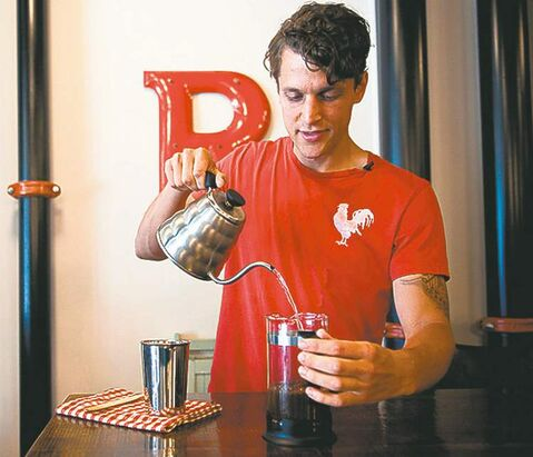 Barista Kyle Wilson mixes cold water and coffee grinds in a French press while making cold brew  coffee.