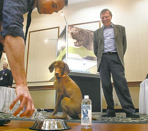 Barrett Peitsch mixes StrixNB with water for his dog Leo as Gord Froehlich, president of Kane Biotech, looks on.