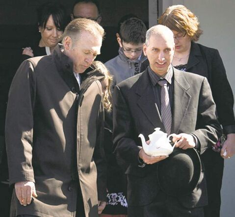 Wade Langham leaves church  with his mother's ashes.