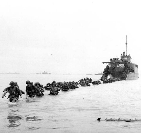 U.S. reinforcements wade through the surf at  Normandy.