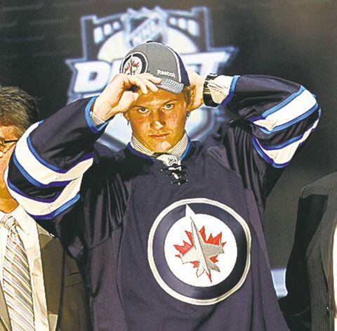 Jacob Trouba, center, a defenseman, pulls on a Winnipeg Jets cap after being chosen ninth overall in the first round of the NHL hockey draft on Friday, June 22, 2012, in Pittsburgh. (AP Photo/Keith Srakocic)