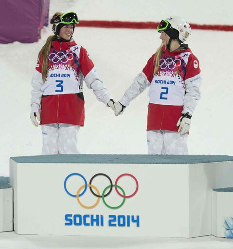Canada's Justine Dufour-Lapointe and Chloe Dufour-Lapointe hold hands claiming their gold and silver Saturday February 8, 2014 in Sochi, Russia.