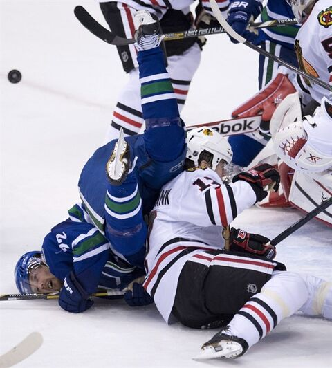 Vancouver Canucks left wing Daniel Sedin (22) goes head over heels over Chicago Blackhawks defenceman Sheldon Brookbank (17) in Vancouver, Jan. 29, 2014. THE CANADIAN PRESS/Jonathan Hayward
