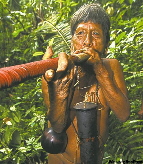 Waorani tribal member, demonstrating the blowgun, which is used to hunt in the jungle. He's wearing a container around his neck which holds the poisonous spears or darts.