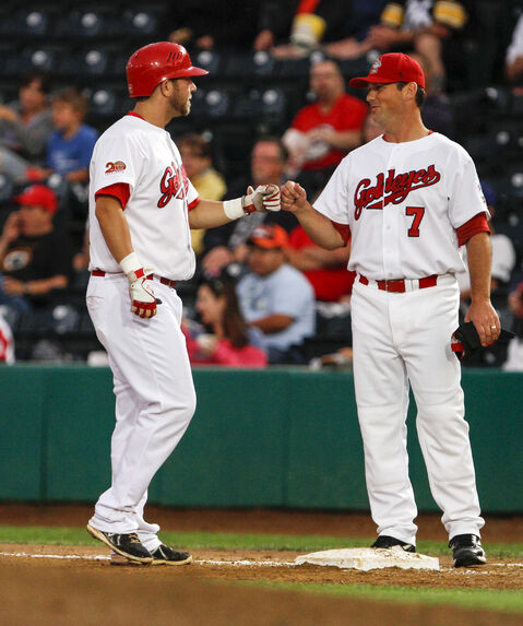 Goldeyes' Casey Haerther (left) bumps fists with hitting coach Tom Vaeth.