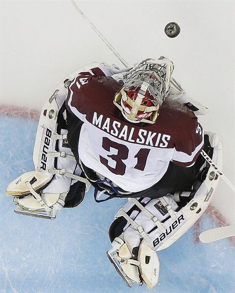 Latvia goaltender Edgars Masalskis blocks a shot on the goal during the third period of the 2014 Winter Olympics men's ice hockey game against Switzerland at Shayba Arena, Wednesday, Feb. 12, 2014, in Sochi, Russia. (AP Photo/Matt Slocum)
