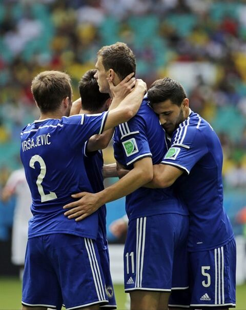 Bosnia's Edin Dzeko, center, is greeted by his teammates after scoring the opening goal during a group F World Cup soccer match between Bosnia and Iran at the Arena Fonte Nova in Salvador, Brazil, Wednesday, June 25, 2014. (AP Photo/Fernando Llano)