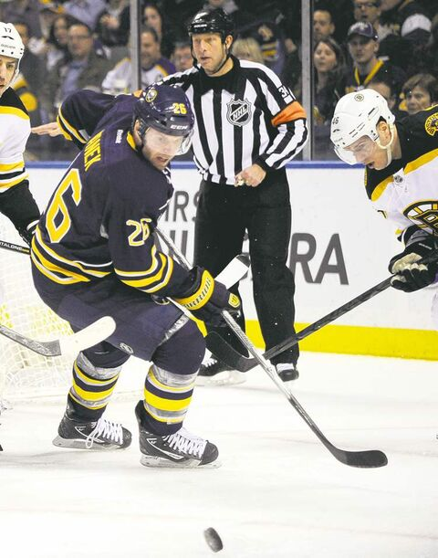 Buffalo Sabres' Jochen Hecht (55), of Germany, battles with Boston Bruins left winger Milan Lucic (17) as Sabres' left winger Thomas Vanek (26), of Austria, eyes the puck during the second period of an NHL hockey game in Buffalo, N.Y., Friday, Feb. 15, 2013. (AP Photo/Gary Wiepert)