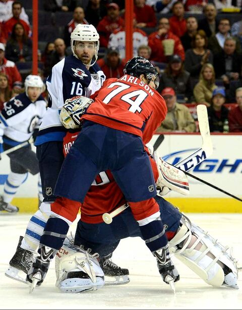 Jets captain Andrew Ladd and Washington Capitals defenceman John Carlson  sandwich Capitals goalie Braden Holtby in the first period Tuesday. Ladd and his linemates carried a disproportionate load in the scoring department. That has to change for the Jets to move forward.