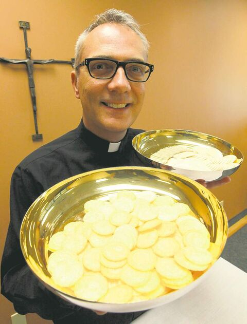 Father Darrin Gurr of St. Gianna Beretta Molla Roman Catholic Church with low-gluten communion wafers.