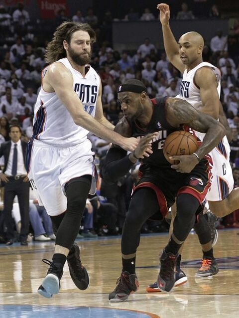 Miami Heat's LeBron James, right, is fouled by Charlotte Bobcats' Josh McRoberts, left, during the second half in Game 3 of an opening-round NBA basketball playoff series in Charlotte, N.C., Saturday, April 26, 2014. The heat won 98-85. (AP Photo/Chuck Burton)