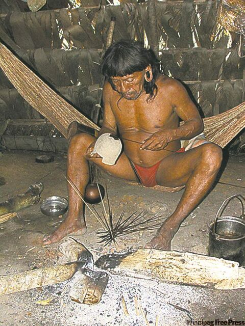 A Waorani tribe member makes curari poison for the tips of the darts used in the blowguns for hunting.