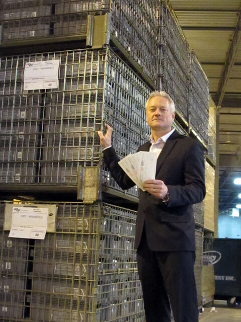 General Manager Doug Wiebe stands beside over 225,000 cheques totaling over $54.9 million to be mailed today.
