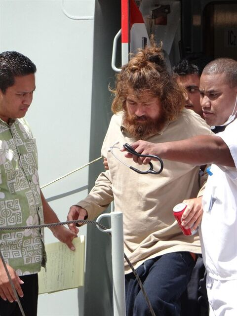 In this Feb. 3, 2014 photo, a man who identifies himself as Jose Salvador Alvarenga, center, gets off a ship in Majuro, the Marshall Islands, after he was rescued from being washed ashore on the tiny atoll of Ebon in the Pacific Ocean. Alvarenga told the U.S. Ambassador in the Marshall Islands Tom Armbruster and the nation's officials that he left Mexico in December 2012 for a day of shark fishing and ended up surviving 13 months on fish, birds and turtles before washing ashore on the remote Marshall Islands thousands of miles (kilometers) away. (AP Photo/Marshall Island Journal) MARSHALL ISLANDS OUT