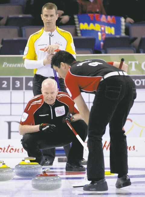 Manitoba skip Jeff Stoughton  watches as Ontario skip Glenn  Howard barks orders at sweeper Craig Savill on Sunday night.