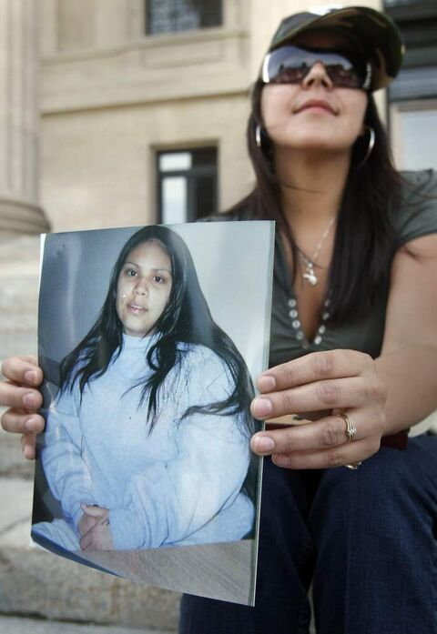 A family member of Cherisse Houle holds a photograph of her at a vigil at in 2009. Cherisse Houle was 17 in 2009. No one has been charged with her slaying.