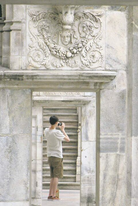 A man takes a picture on the rooftop of the Milan cathedral in Milan, Italy.