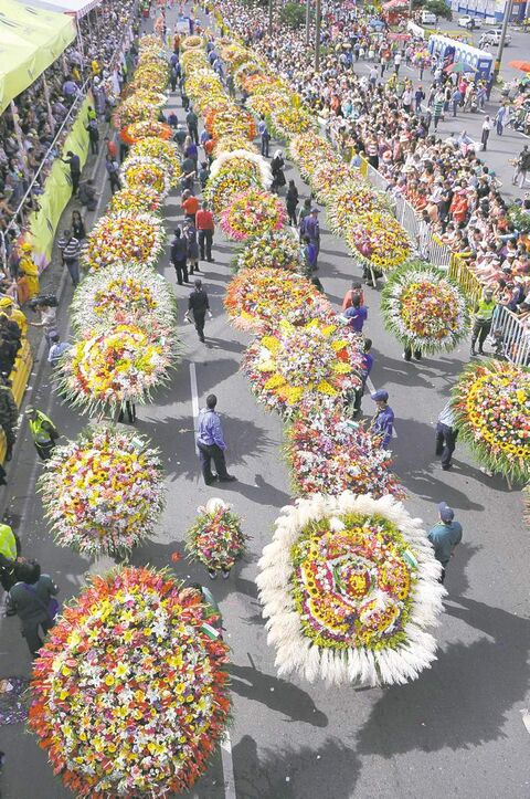 People stand amongst flower arrangements during the annual  festival of flowers in Medellin.