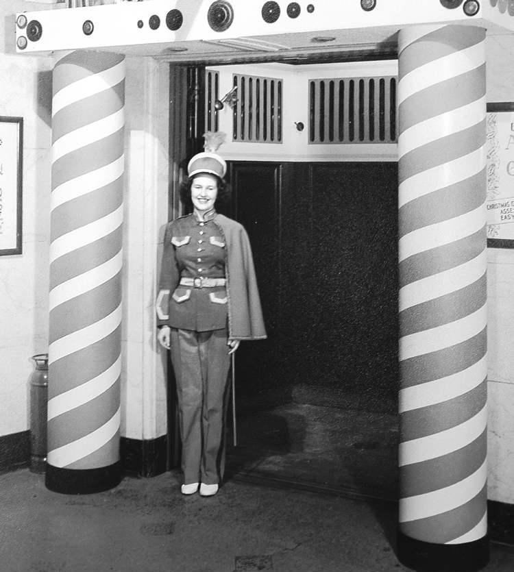 An elevator girl dressed in a toy soldier costume runs the Toy Town Express elevator at the downtown Bay in 1947. - Hudson