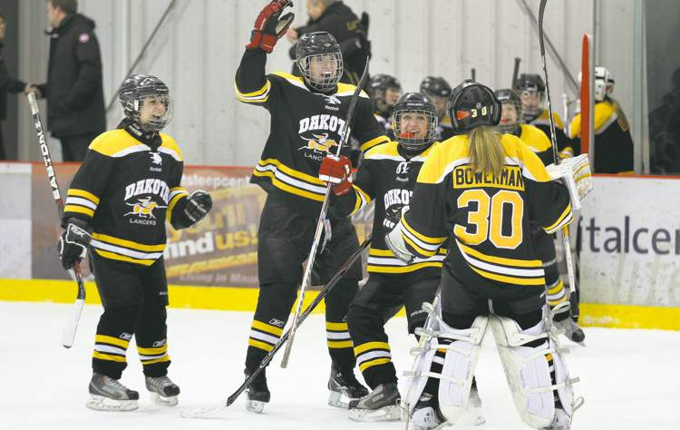 Phil Hossack / Winnipeg Free Press Jubilant Lancers rally around netminder Kelsey Bowerman after defeating the Louis Riel Voyagers Thursday at the MTS Iceplex.