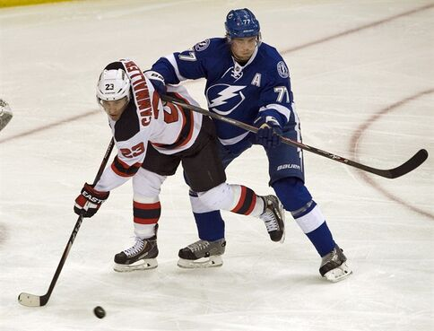 New Jersey Devils' Mike Cammalleri (23) and Tampa Bay Lightning's Victor Hedman (77) vie for the puck during the first period of an NHL hockey game Tuesday, Oct. 14, 2014 in Tampa, Fla. Hedman left the second period of Saturday's game against the Vancouver Canucks with an upper-body injury and did not return. THE CANADIAN PRESS/AP/Steve Nesius