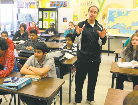 Teacher Dan Beettam teaches money and finance topics to a class at Valley Gardens Middle School.