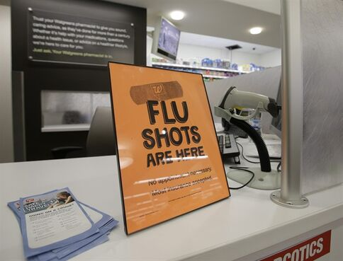 A sign telling customers that they can get a flu shot in a Walgreen store is seen Tuesday, Sept. 16, 2014, in Indianapolis. The nation's biggest drugstores and retailers are grabbing larger chunks of the immunization market, giving customers more convenient options to protect themselves against the flu, pneumonia and more than a dozen other illnesses. (AP Photo/Darron Cummings)