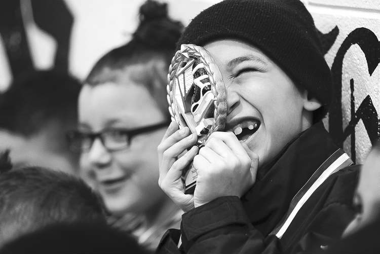 Nicco Botelho, 8, peeks though his hockey medal at the Norquay  Community Centre wrap-up party.