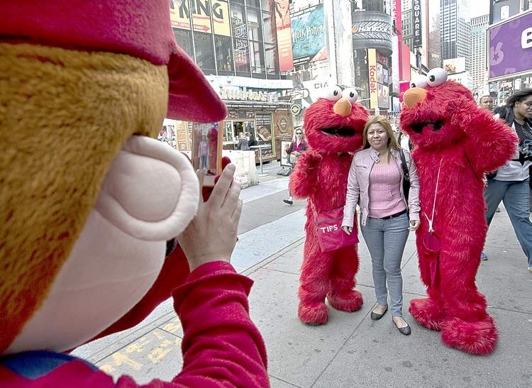 Some rather ratty-looking Elmos pose with a tourist in Times Square.