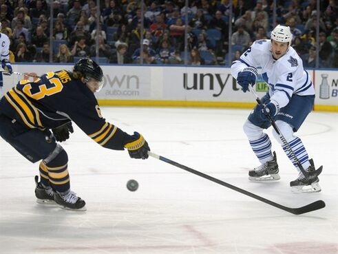 Toronto Maple Leafs' Eric Brewer (2) passes the puck as Buffalo Sabres' Tyler Ennis defends during the first period of an NHL hockey game Wednesday, April 1, 2015, in Buffalo, N.Y. (AP Photo/Gary Wiepert)