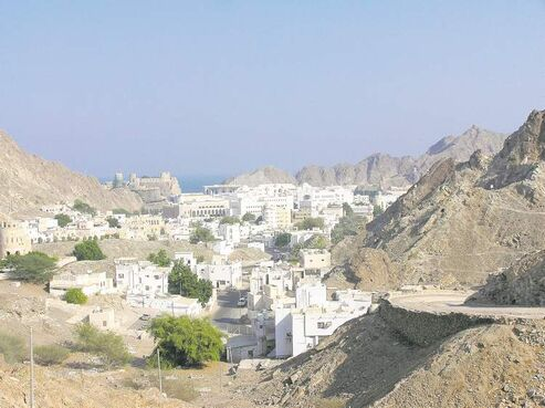 View of Old Muscat, with Sultan Qaboos's Al Alam Palace in the far distance, centre, flanked by two old forts built during the Portuguese occupation.