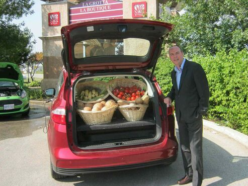 Ford of Canada brand and EV marketing manager Dean Geddes with a 2014 Ford C-Max Energi loaded with baskets of vegetables. Ford is currently utilizing agricultural waste material like rice hulls and wheat residue in its manufacturing process.