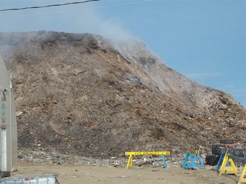 A fire smoulders at a dump in Iqaluit, Nunavut, on July 16, 2014. Although no flames are visible, the stubborn dump fire has been smouldering since May 20. THE CANADIAN PRESS/HO - Iqaluit Fire Department